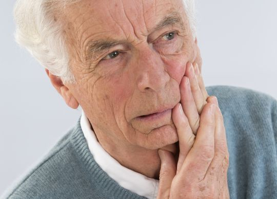 Why do dentures cause problems while speaking?